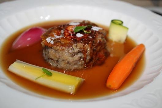 Manitas de cerdo con foie gras micuit y trufa negra, fondo de manitas y jamón, verduritas